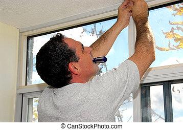 Handyman - Man installing window blinds in a house