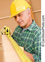 Handyman mature carpenter measure wooden beam