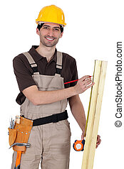 Handyman measuring a wooden plank