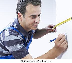 Handyman measuring the wall