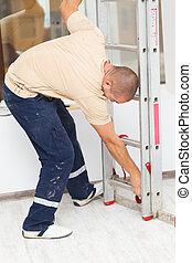 Handyman mounting a step ladder before work.