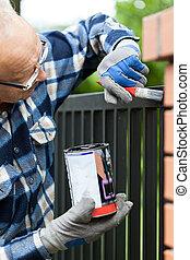 Handyman painting metal fence