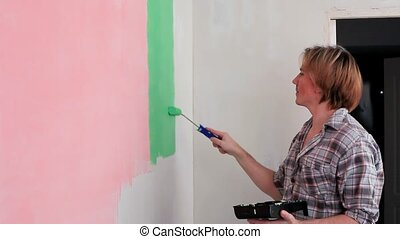 Handyman Painting Wall - Man paint roller paint stripes on...