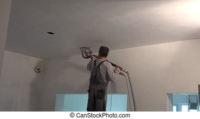 Handyman polishing ceiling with grinding sandpaper machine. ...