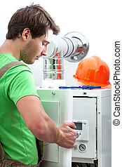 Handyman repairing boiler in a boiler room
