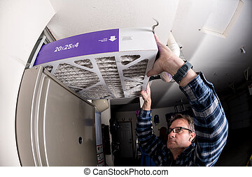 Handyman replaces the filter in the hot air furnace at a home