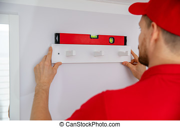 handyman services - man installing towel hanger on the wall