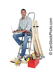Handyman sitting on a ladder with laptop