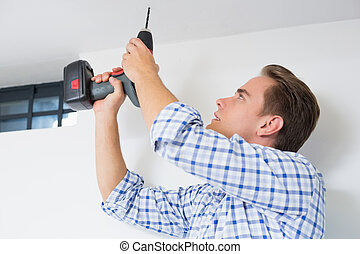 Side view of a young handyman using a cordless drill to the ceiling