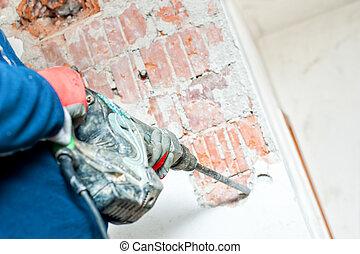 handyman using a jackhammer to distroy concrete interior walls
