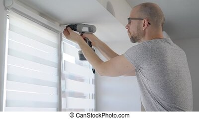 Handyman using drill to install mechanism for new blinds. He...