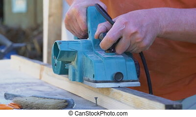Handyman using electric wood planer outdoors.