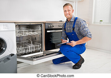 Handyman With Clipboard Looking At Dishwasher - Young...
