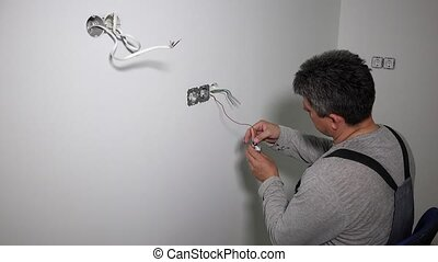 Handyman with cordless drill screw electrical outlet. Static...