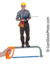 Handyman with drill standing on giant hacksaw