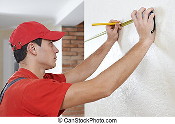 Handyman with measuring tape - Young professional handyman...