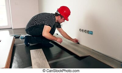 handyman with red helmet installing wooden floor in new...