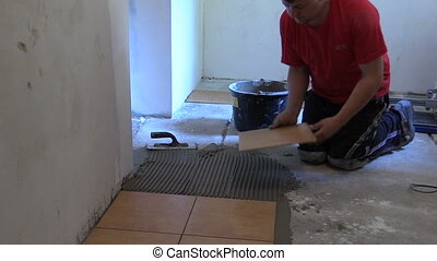 Handyman worker place floor tiles. Home improvement,...