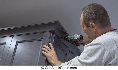 Handyman working instal brad nail gun to Crown Moulding wall...
