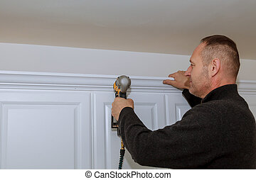 Handyman working using brad nail gun to Crown Moulding on ...
