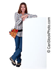 Handywoman standing behind a blank sign