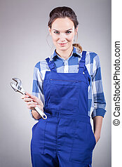 A beautiful handywoman in overalls holding pillers