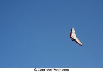Hang Glider - a hang glider soars across a blue sky