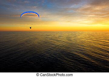 Hang gliding man over sea at sunset