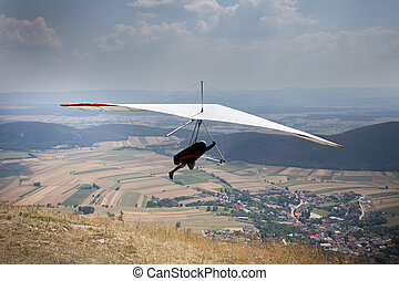 Hang glider jump from top of hill, village and field down in...