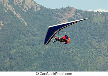 man doing hang-gliding and landing with brake parachute. World air games in Avigliana, Turin, Italy