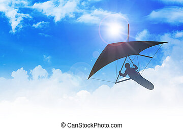 Hang Glider - Silhouette of hang glider flying among clouds