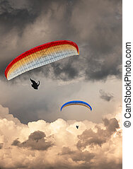 Two hang gliders at sunset with moody sky