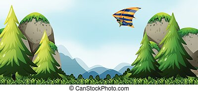 Man doing hang-gliding over the mountains