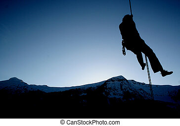 Hangin' out. - A rock climber rappels into the twighlight.