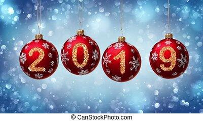 hanging 2019 number glitter Christmas balls on blue bokeh...