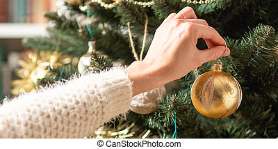 hanging a christmas bauble on tree