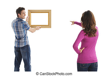 Hanging a picture. Young couple hanging a picture while ...