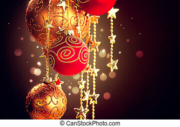 Hanging Christmas baubles and garland over dark background