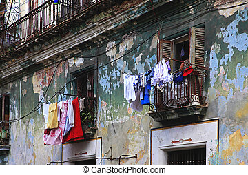 Hanging laundry to dry on balcony in Havana