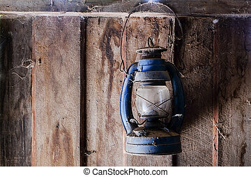 Hanging old lantern with cobweb on wooden wall.
