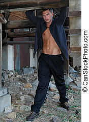 Hanging Out - Young man hangs from beams in abandoned gold...