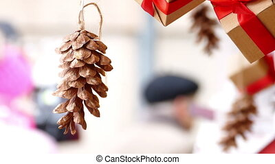 Hanging pine cone and presents with red ribbon in...