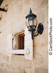 Hanging street lamp in black on the wall by a window with open shutters.