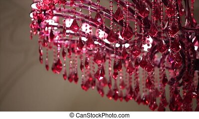 Hanging suspended crystal glass spheres lit up by red light in a dark interior at night