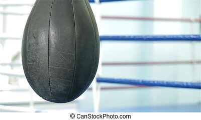 Hanging up punching bag and boxing ring on the background -...