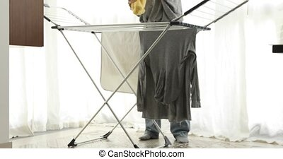 Hanging up washing in a clothes dryer rapid. Crop woman...