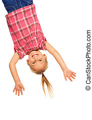 Happy laughing 4 years old girl hanging upside down isolated on white with smile on her face