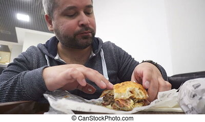 Hangry man eating big hamburger in fast food cafe