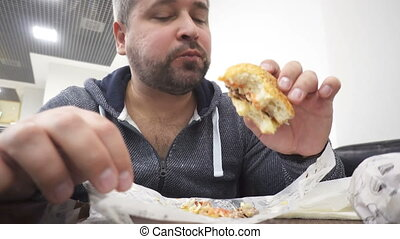 Hangry man eating big hamburger in fast food cafe