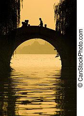 hangzhou - silhouette of people walking on the bridge in...